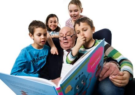 Äldre man läser bok för yngre barn